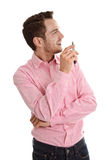 Successful attractive young man in pink looking sideways holding Stock Image