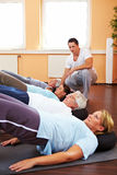 Successful back training. Group doing back exercises in a gym with fitness trainer Stock Photography