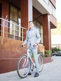 Handsome businessman riding a bicycle on the urban background. Healthy lifestyle concept. Copy space. royalty free stock photo