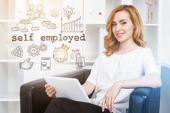 Successful and beautiful self employed woman. Charming red haired woman sitting in black armchair in office near a self employed text and icons drawing. Toned stock photo