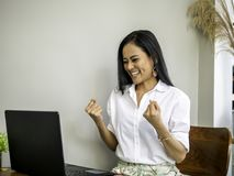Successful beautiful young asian entrepreneurs achieving goals. She is raising two hands in fists with exciting and smiling face while working with a notebook Stock Image
