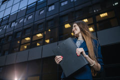 Successful beautiful young business woman standing against a background of buildings and holding folder. Successful beautiful young business woman standing Stock Images