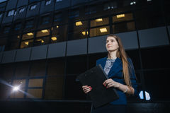 Successful beautiful young business woman standing against a background of buildings and holding folder. Stock Images
