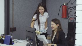 Business people working in office. Successful bid. Two happy businesswoman rejoice at successful transaction and grown currency rate sitting in the office at the stock video