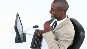 Successful black businessman. Sitting at his desk against white background stock video