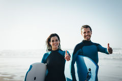 Successful bodyboard couple. Successful couple of surfers. Surfing and outdoor sport lifestyle concept. Woman and men after bodyboarding royalty free stock photography