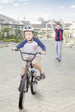 Successful boy riding a bike with his dad. Portrait of successful little boy riding a bicycle on the road with happy father on the back, shot outdoors Stock Photography