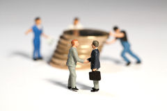 Successful Business Arrangement. Miniature toy figures of businessmen shaking hands in front of a large pile of Euro coins being moved by workmen, macro with Stock Image
