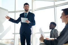 Successful Business Coach. Portrait of handsome successful businessman pointing at whiteboard  and smiling during presentation meeting Royalty Free Stock Photos