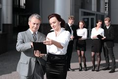 Business colleagues with documents standing in front of the office building . royalty free stock image