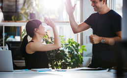 Successful business colleagues giving high five. Shot of happy and successful business colleagues giving high five in office Royalty Free Stock Photos