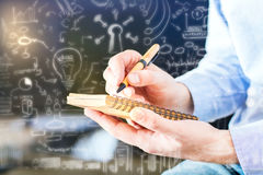 Successful business concept. Businessman writing in notepad with creative business sketch pattern. Successful business ideas concept Royalty Free Stock Image