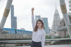 Successful business concept. Portrait of cheerful young Asian businesswoman smiling and raising hands up at urban building backgro royalty free stock photos