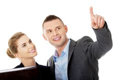 Successful business couple pointing away Royalty Free Stock Photo