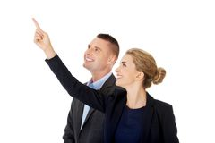 Successful business couple pointing away Stock Photo