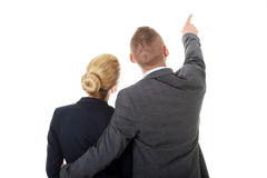 Successful business couple pointing away Royalty Free Stock Photos