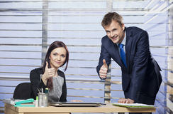 Successful business couple showing thumbs up. In the office royalty free stock image