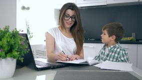 Successful business at home, young mom in glasses makes notes in notebook sitting on kitchen and then happily hugs son stock video footage