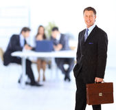 Successful business man. Standing with his staff in background at office stock photos