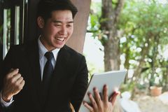 Successful business man checking tablet message & raise fist wit. H happiness and gladness outside office building. male startup entrepreneur enjoy success in stock image