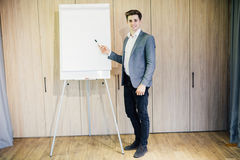 Successful business man with a flip chart in a presentation in modern office Royalty Free Stock Image