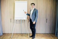 Successful business man with a flip chart in a presentation in modern office Stock Photography