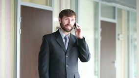 Successful business man having cell telephone conversation while standing in office interior, stock footage