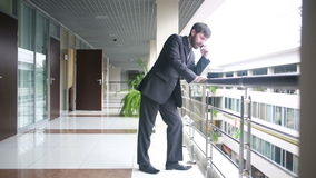 Successful business man having cell telephone conversation while standing in office interior,