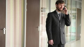 Successful business man having cell telephone conversation while standing in office interior, stock video