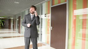 Successful business man having cell telephone conversation while standing in office interior, stock video footage