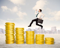 Successful business man jumping up on gold coin money Royalty Free Stock Image