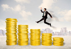 Successful business man jumping up on gold coin money. Concept stock images