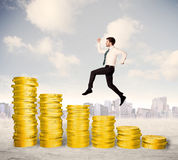 Successful business man jumping up on gold coin money Royalty Free Stock Photo