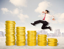 Successful business man jumping up on gold coin money Stock Photo
