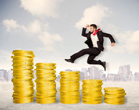 Successful business man jumping up on gold coin money Royalty Free Stock Photos