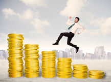 Successful business man jumping up on gold coin money. Concept royalty free stock photography