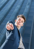 Successful business man pointing at camera over office building background Royalty Free Stock Photo
