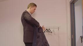 Successful business man putting coat and and leavIng business office. Successful business man putting coat and leavIng business office. Young business manager stock footage
