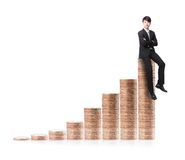 Successful business man sitting on money stairs Stock Images