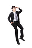 Successful business man sitting on something. And look to empty copy space isolated against white background, asian male model Stock Photography
