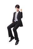 Successful business man sitting on something Stock Images