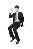 Successful business man sitting on something Royalty Free Stock Images