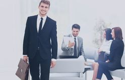 Successful business man standing with his staff in background at. Handsome business men standing with his collegues in background at office Stock Photos