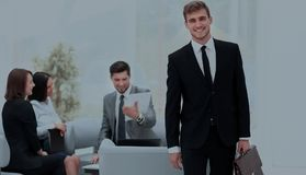 Successful business man standing with his staff in background at. Handsome business men standing with his collegues in background at office Royalty Free Stock Photo