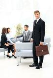 Successful business man standing with his staff in background at Royalty Free Stock Image