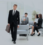 Successful business man standing with his staff in background at Royalty Free Stock Photo