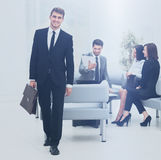 Successful business man standing with his staff in background at. Handsome business men standing with his collegues in background at office Royalty Free Stock Image