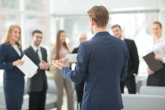 Successful business man standing with his staff in background at Royalty Free Stock Photography