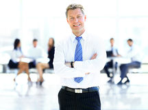 Successful business man standing with his staff. In background at office Stock Photos