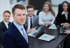 Successful business man standing with his staff in background at office Royalty Free Stock Image